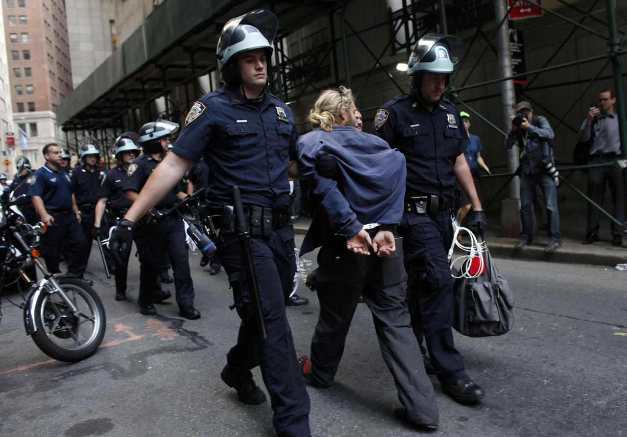 Police officers lead a man away during an Occupy Wall Street march, Monday, Sept. 17, 2012, in New York. A handful of Occupy Wall Street protestors were arrested during a march on the New York Stock Exchange on the anniversary of the grass-roots movement. (AP Photo/Jason DeCrow)