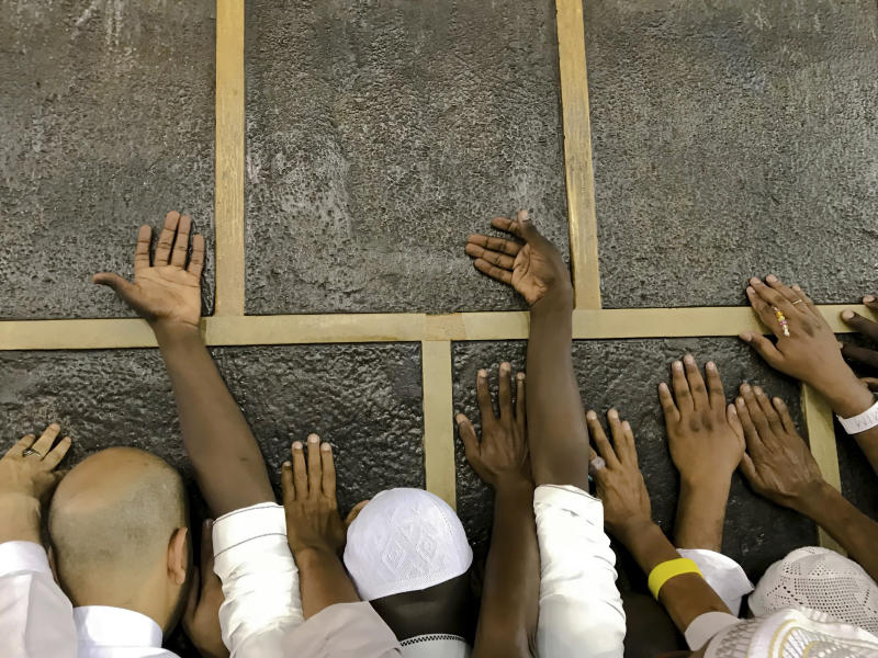 Muslim pilgrims touch the Kaaba stone, the cubic building at the Grand Mosque, as they pray ahead of the annual Hajj pilgrimage in the Muslim holy city of Mecca, Saudi Arabia, Friday, Aug. 17, 2018. The annual Islamic pilgrimage draws millions of visitors each year, making it the largest yearly gathering of people in the world. (AP Photo/Dar Yasin)