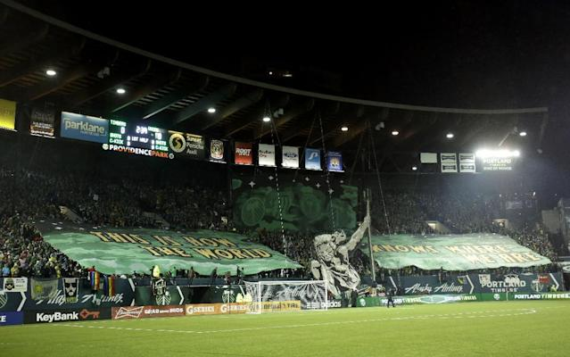 Portland Timbers fans raise banners and signs before an MLS soccer game against the Philadelphia Union at Provdence Park in Portland, Ore., Saturday, March 8, 2014. (AP Photo/Don Ryan)