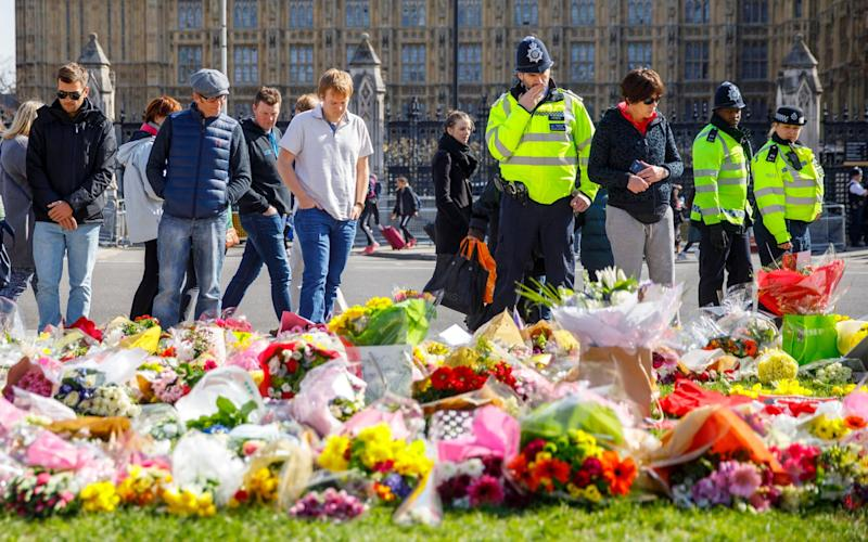 Members of public and police officers pay their respects to the victims of Westminster terror attack in Parliament Square, London  - Credit:  Tolga Akmen/LNP