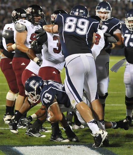 Connecticut's Lyle McCombs (43) pokes through for a touchdown against Massachusetts in the first half of an NCAA college football game in East Hartford, Conn., Thursday, Aug. 30, 2012. (AP Photo/Jessica Hill)