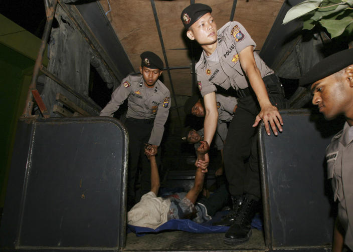 Indonesian police officers carry the body of an illegal migrant from Myanmar upon arrival at a hospital in Medan, North Sumatra, Indonesia Friday, April 5, 2013. Police said a violent brawl between Buddhist and Muslim asylum seekers from Mynamar in an immigration detention center in Belawan of North Sumatra early Friday leaving eight dead and 15 injured. (AP Photo/Binsar Bakkara)