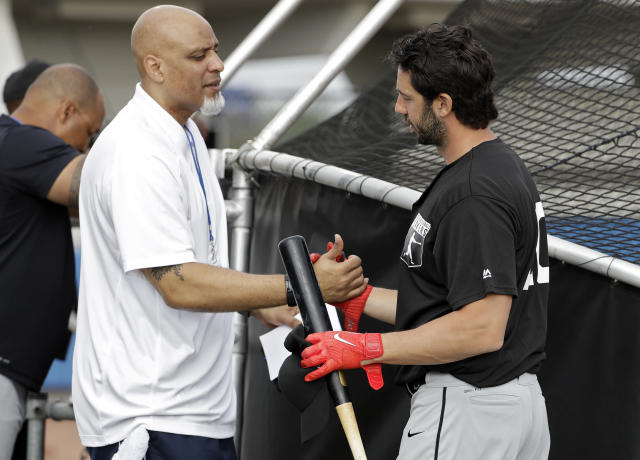 Tony Clark, left, head of the Major League Baseball Players Association, shakes hands with free agent player Chris Colabello before an exhibition baseball game against JR East, a Japanese amateur team, Tuesday, Feb. 27, 2018, in Bradenton, Fla. (AP Photo/Chris O'Meara)