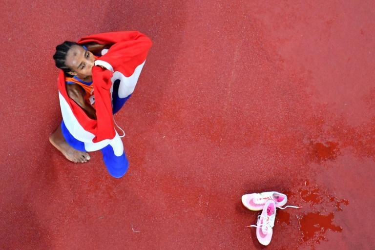 Sealed with a kiss: Dutch runner Sifan Hassan celebrates her 5,000m gold medal at the Olympics on Monday