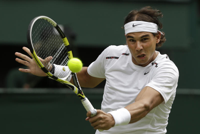 """FILE - This June 26, 2012 file photo shows Rafael Nadal of Spain returning a shot to Thomaz Bellucci of Brazil during a first round men's singles match at the All England Lawn Tennis Championships at Wimbledon, England. Nadal has confirmed he is ready to return to competitive tennis at the end of the month in an exhibition tournament in Abu Dhabi, following a six-month break to recover from a knee injury. The 11-time Grand Slam champion said on his Facebook page Tuesday, Dec. 11, 2012, that he """"can't wait to get back on court in Abu Dhabi,"""" and that he """"would love to get my hands on the trophy again this year!"""" (AP Photo/Anja Niedringhaus, File)"""