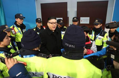 Ice Hockey – Pyeongchang 2018 Winter Olympics – Women Preliminary Round Match - Korea v Japan - Kwandong Hockey Centre, Gangneung, South Korea – February 14, 2018 - Kim Jong-un impersonator is surrounded by security personnel. REUTERS/Lucy Nicholson