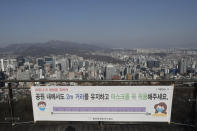 A banner showing a social distancing instruction is seen at a park, with a backdrop of a city view in Seoul, South Korea on Dec. 24, 2020. South Korea had seemed to be winning the fight against the coronavirus: Quickly ramping up its testing, contact-tracing and quarantine efforts paid off when it weathered an early outbreak without the economic pain of a lockdown. But a deadly resurgence has reached new heights during Christmas week, prompting soul-searching on how the nation sleepwalked into a crisis. (AP Photo/Lee Jin-man)