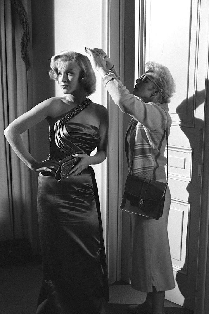 <p>Marilyn Monroe's famous platinum blonde curls are tended to by someone in the makeup department, while the actress films a scene for <em>How to Marry a Millionaire.</em></p>