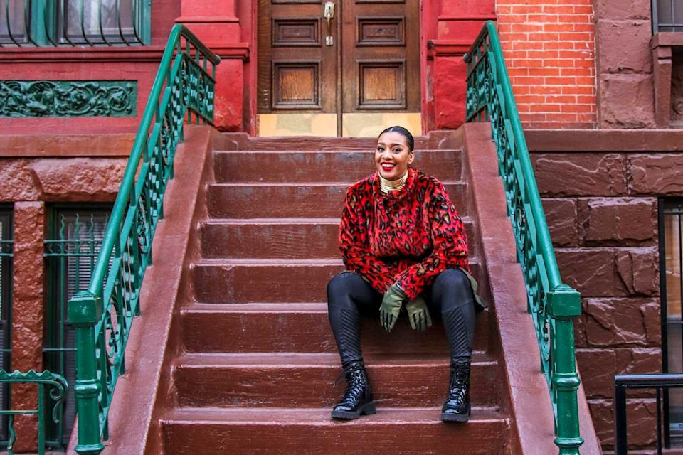 Evita Robinson sitting on the steps of a townhouse in Harlem, New York