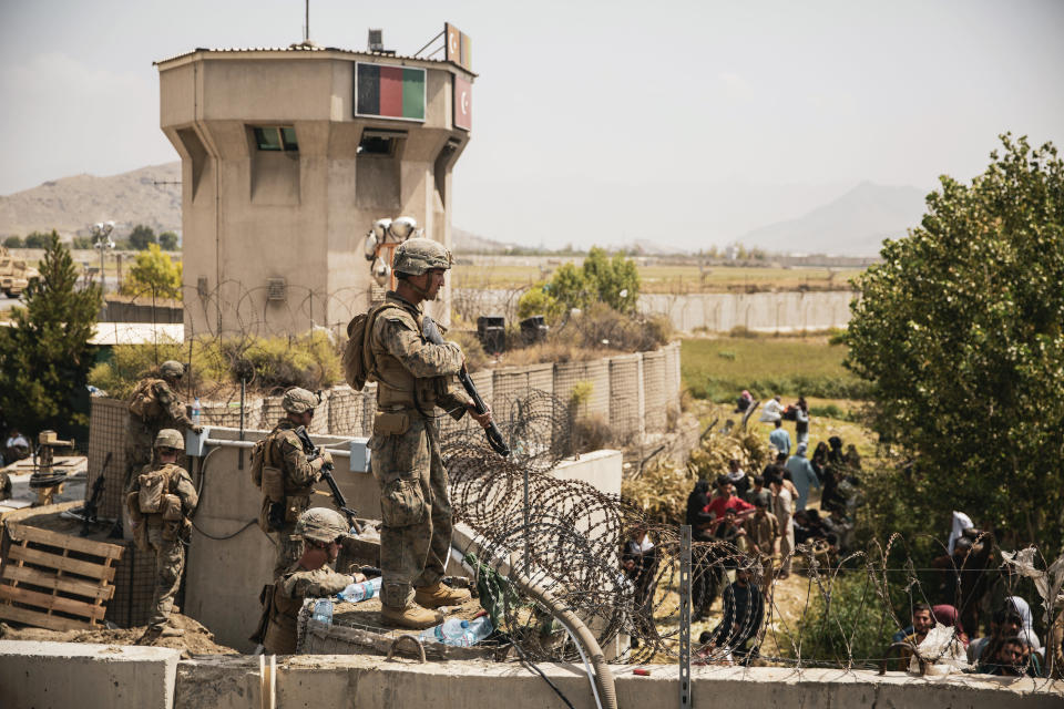 In this image provided by the U.S. Marine Corps, Marines assist with security at an evacuation control checkpoint during an evacuation at Hamid Karzai International Airport in Kabul, Afghanistan, Friday, Aug. 20, 2021. (Staff Sgt. Victor Mancilla/U.S. Marine Corps via AP)