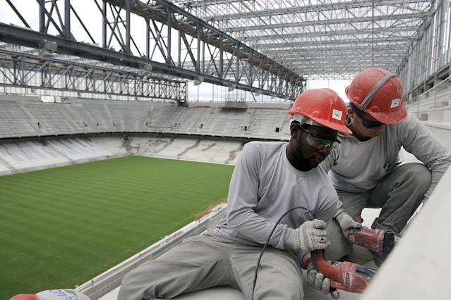 Personnel work on the construction of Arena da Baixada in Curitiba, Brazil, Tuesday, Feb. 18, 2014. The southern Brazilian city will host matches during this year's World Cup despite serious problems in the renovation of its stadium that put it on the brink of becoming the first venue ever to be kicked out because of delays, FIFA Secretary General Jerome Valcke said Tuesday. (AP Photo/Denis Ferreira Netto)