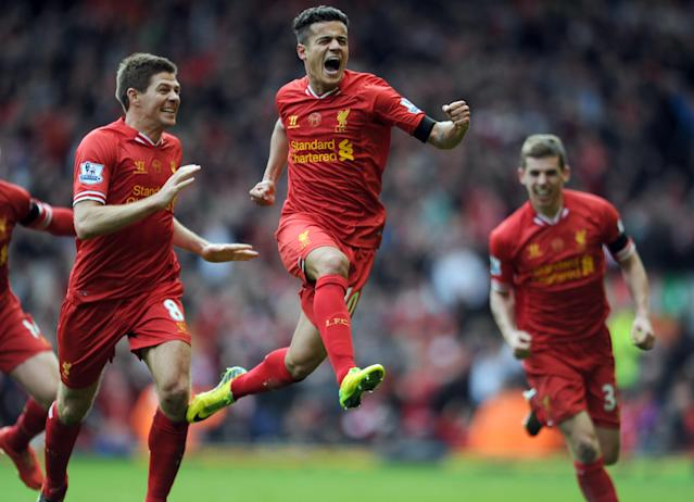 Liverpool's Philippe Coutinho, centre, celebrates with teammate Steven Gerrard, left, after he scored the third goal of the game for his side during their English Premier League soccer match against Manchester City at Anfield in Liverpool, England, Sunday April. 13, 2014. (AP Photo/Clint Hughes)