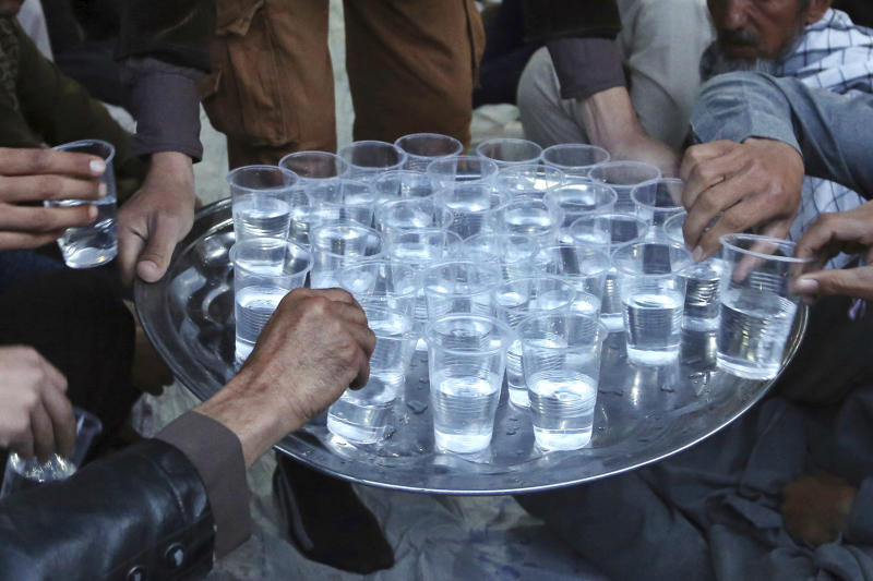 FILE - In this Thursday, May 17, 2018, file photo, people take glasses of water from a tray in Kabul, Afghanistan. On Friday, Feb. 28, 2020, The Associated Press reported on stories circulating online incorrectly asserting that keeping your mouth and throat moist will help you avoid getting the new coronavirus. Dr. William Schaffner, an infectious-diseases expert at Vanderbilt University, says while medical professionals typically recommend keeping up fluid intake, drinking more water will not keep anyone from catching the virus. (AP Photo/Rahmat Gul)