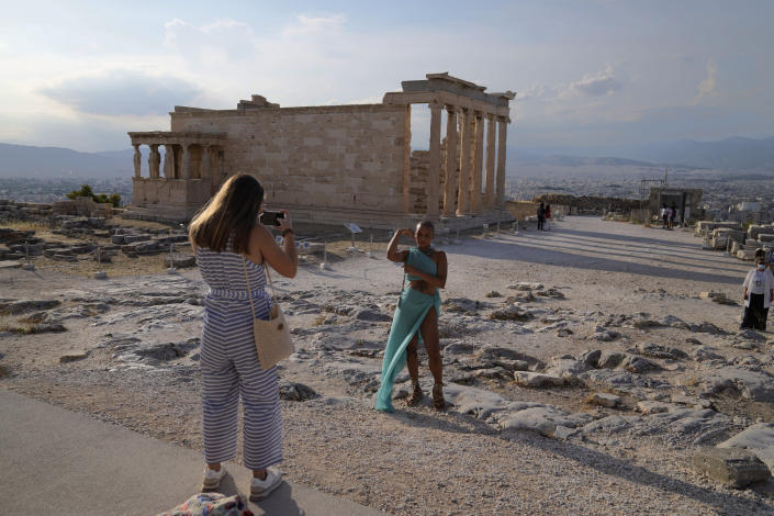 FILE - In this Tuesday, June 8, 2021 file photo, a tourist take photos at the Parthenon temple during a media tour for the Foreign Correspondents organised by the Greek Cultural Ministry at the Acropolis hill in Athens. Europe is opening up to Americans and other visitors after more than a year of COVID-induced restrictions. European governments hope to lure back tourists - and their dollars - back to the continent's trattorias, vistas and cultural treasures. (AP Photo/Thanassis Stavrakis, File)