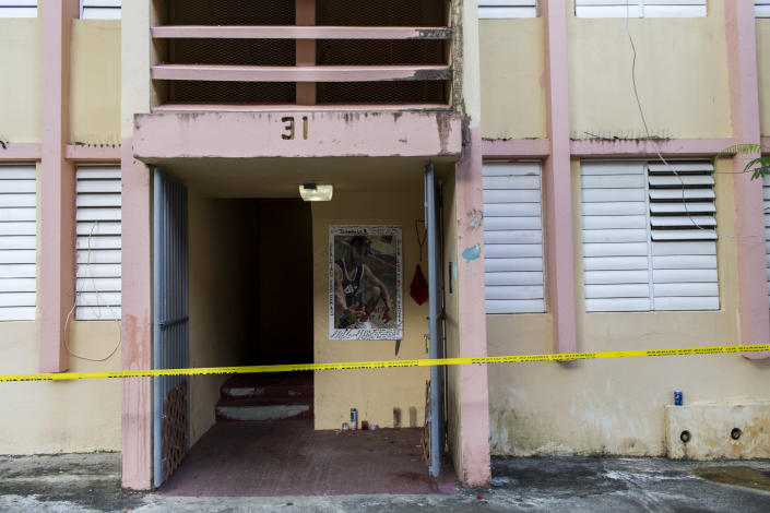 Police tape secures the area of a makeshift altar at the home of a youth that was murdered on Sept. 11, at the scene of a multiple killing in San Juan, Puerto Rico, Tuesday, Oct. 15, 2019. Several people are reported dead following a shooting in the Rio Piedras neighborhood of San Juan. (AP Photo/Dennis M. Rivera Pichardo)