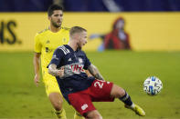 New England Revolution defender Alexander Buttner (28) passes the ball ahead of Nashville SC defender Eric Miller, left, during the first half of an MLS soccer match Friday, Oct. 23, 2020, in Nashville, Tenn. (AP Photo/Mark Humphrey)