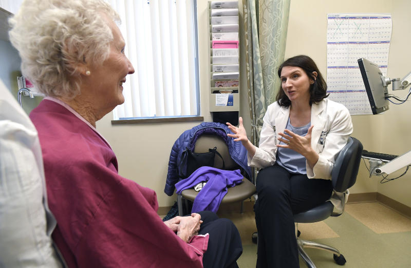 In this Monday, March 4, 2019 photo, Dr. Allison Magnuson, Geriatric Oncology and Breast Oncology at Wilmot Cancer Institute, right, speaks with patient Nancy Simpson at the Pluta Cancer Center in Rochester, N.Y. Instead of assuming that elderly patients are too frail for treatment or recommending harsh drugs tested only in younger patients, cancer doctors are taking time to evaluate their physical and mental fitness, along with emotional and social well-being. (AP Photo/Adrian Kraus)