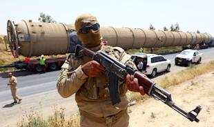 A Kurdish peshmerga fighter stands guard as new equipment arrives at Kalak refinery on the outskirts of Irbil, Iraq, Monday, July 14, 2014, as Kurdish authorities try to help ease the fuel shortage. Islamic militants have laid siege to Iraq's largest oil refinery in the city of Beiji. (AP Photo)