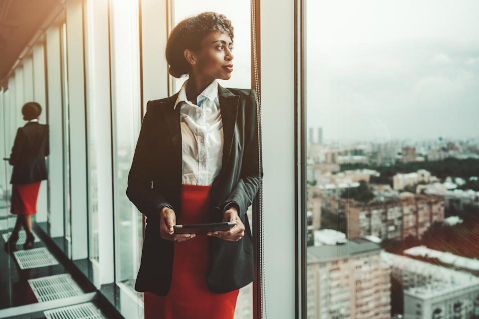An African-American woman entrepreneur a digital tablet is leaning against a panoramic window of an office business skyscraper and looking in a distance; biracial businesswoman with a tablet pc