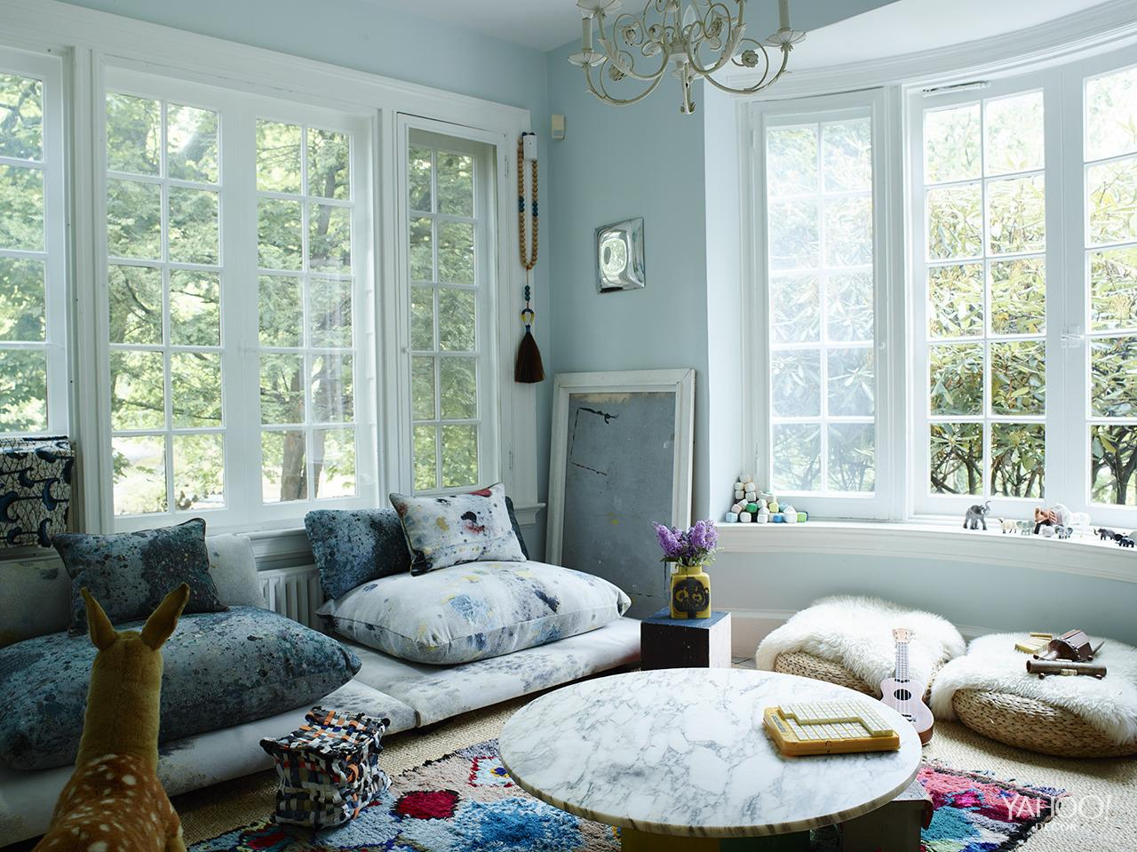 """<p>""""People love hanging out in this room. We call it the kid room, but it is beloved by adults and kids alike. I designed the Chicklet Formation sofa, which is upholstered with """"Dropcloth"""" fabric designed by <a href=""""http://www.martynthompsonstudio.com/"""">Martyn Thompson</a>. The thing I love most about this room is that everything is low to the floor, '70s style. We took a formal space and reimagined it as something friendlier. We rarely let food in here, but if something spills on the couch, who cares? The fabric is made to look like splattered paint anyway.""""<br /></p>"""