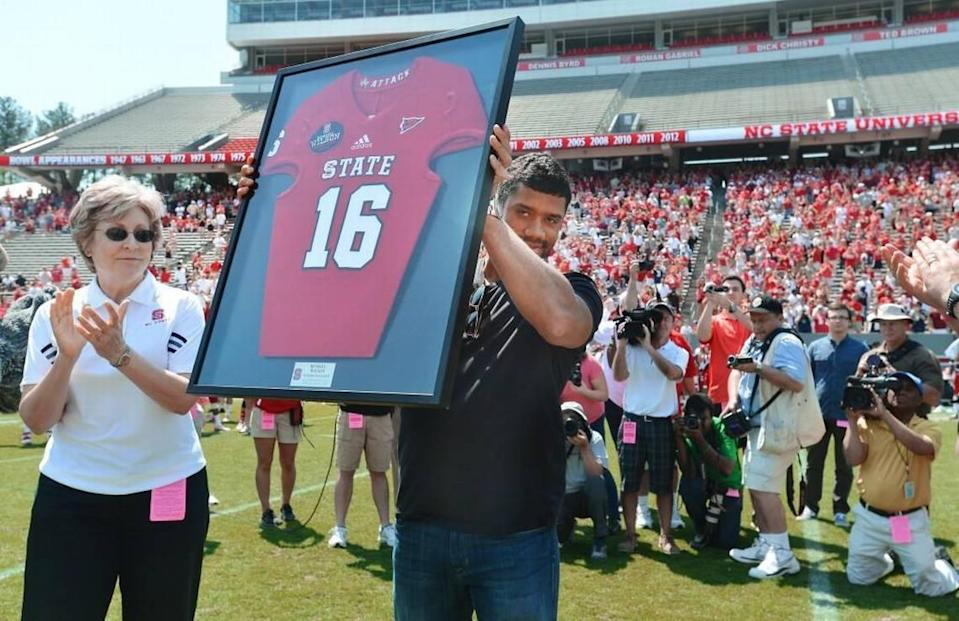 Former N.C. State quarterback and Super Bowl XLVIII champ Russell Wilson holds up his framed No. 16 Wolfpack jersey as he was honored on April 12, 2014.