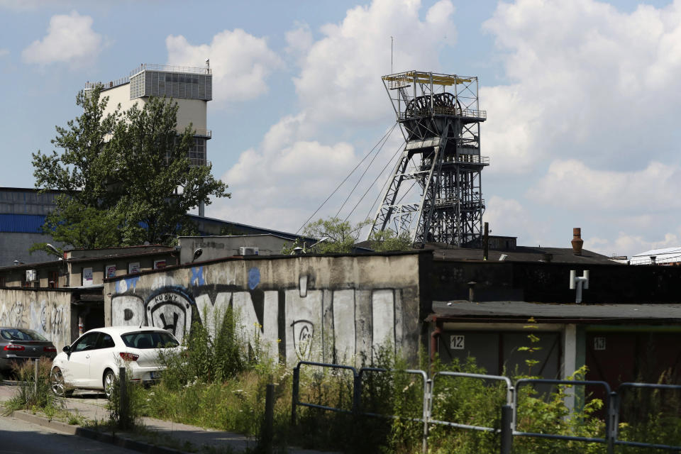 Cars sit outside the closed Wujek coal mine in Katowice, Poland, Saturday, July 4, 2020. The coronavirus has ripped through Poland's coal mines, where men descend deep underground in tightly packed elevators and work shoulder-to-shoulder. The virus hot spots, centered in the southern Silesia region, have paralyzed an already-troubled industry, forcing many to stay home from work and triggering a three-week closure of many state-run mines. (AP Photo/Czarek Sokolowski)