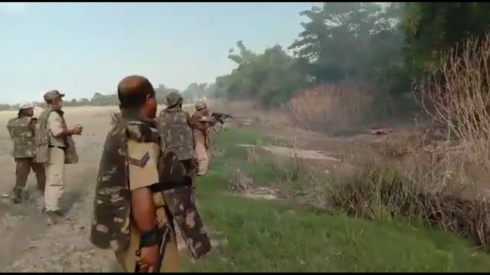 Screengrab from the video showing police in riot gear firing shots at targets from behind bushes  (Screengrab/Ahmer Khan)