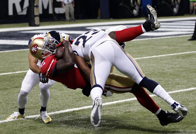 San Francisco 49ers wide receiver Anquan Boldin is brought down by St. Louis Rams cornerback Cortland Finnegan, rear, and safety Rodney McLeod (23) after catching a pass for a 42-yard gain during the second quarter of an NFL football game Thursday, Sept. 26, 2013, in St. Louis. (AP Photo/Tom Gannam)