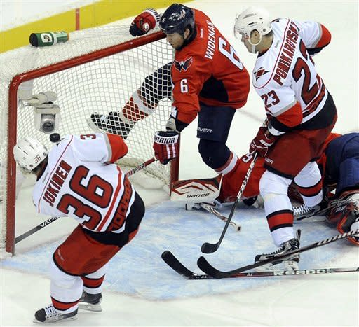 Carolina Hurricanes' Jussi Jokinen (36), of Finland, scores against fallen goalie Tomas Vokoun, laying on the ice, during the second period of their NHL hockey game, Sunday, Jan. 15, 2012, in Washington. Capitals' Dennis Wideman (6) and Hurricanes' Alexei Ponikarovsky (23) eye the puck on the play. (AP Photo/Richard Lipski)