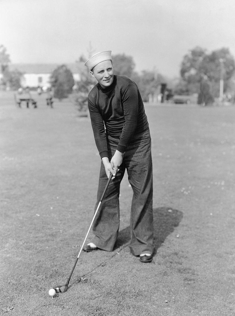 <p>Bing Crosby hits a couple of golf balls during a filming break, circa 1930.</p>