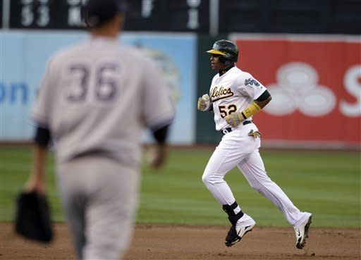 Oakland Athletics' Yoenis Cespedes, right, runs the bases after hitting a two-run home run off New York Yankees' Freddy Garcia (36) in the first inning of a baseball game on Thursday, July 19, 2012, in Oakland, Calif. (AP Photo/Ben Margot)