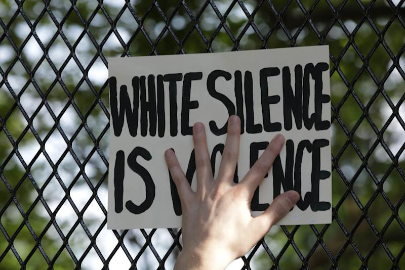 Pictured is a sign on a fence in Washington that says White Silence is Violence, part of the George Floyd protest.