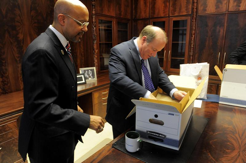 """New Detroit Mayor Mike Duggan unpacks boxes with Melvin """"Butch"""" Hollowell after taking the oath of office, New Years Day, Wednesday, Jan. 1, 2014, at the Coleman Young Municipal Center in Detroit. (AP Photo/The Detroit News, Steve Perez)"""