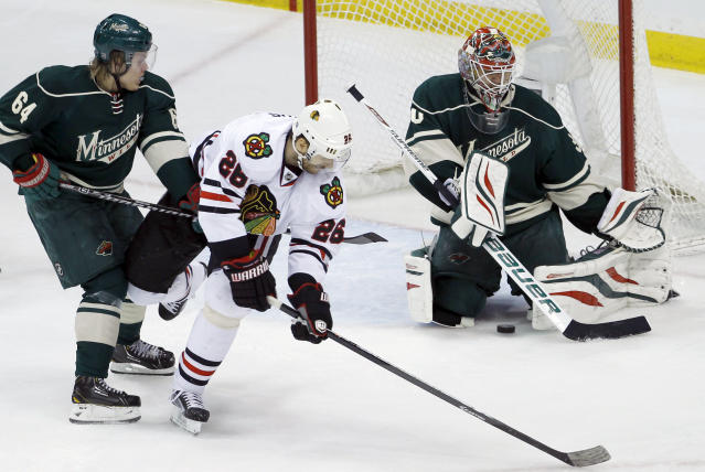 Chicago Blackhawks center Michal Handzus (26), of Czech Republic, gets a shot through the legs of Minnesota Wild goalie Ilya Bryzgalov, right, of Russia, to score in front of Wild center Mikael Granlund (64), of Finland, during the second period of Game 4 of an NHL hockey second-round playoff series in St. Paul, Minn., Friday, May 9, 2014. (AP Photo/Ann Heisenfelt)