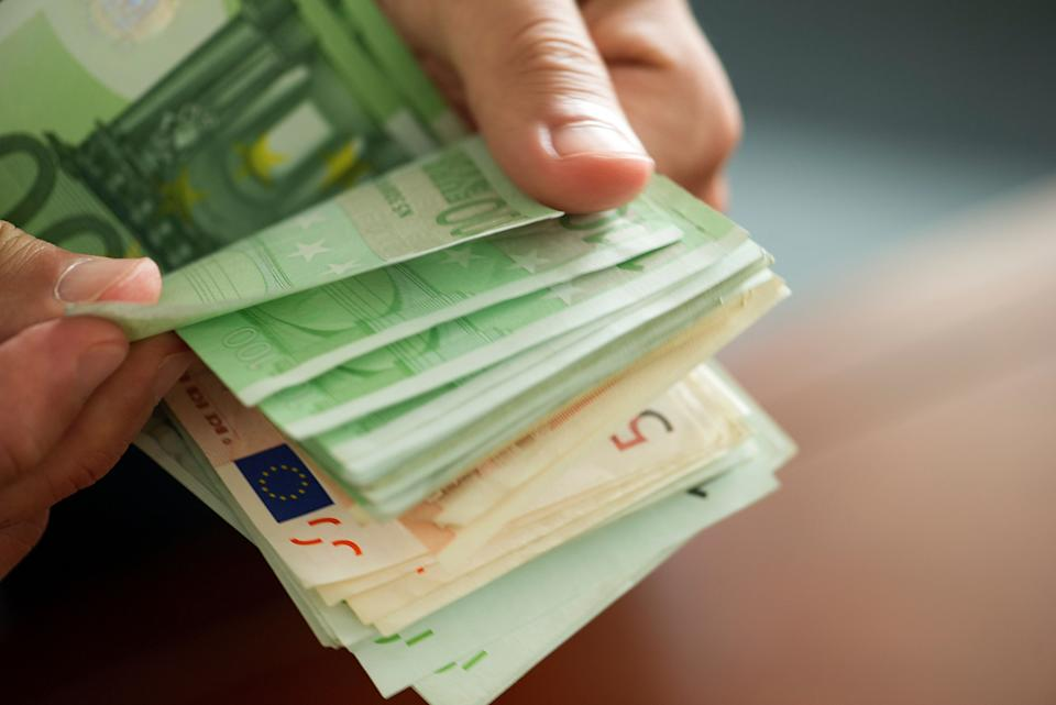 Hands countong stack of money, cropped (Photo: PhotoAlto/Frederic Cirou via Getty Images)