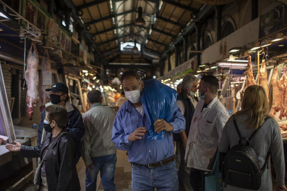 A consumer wearing a protective face mask carries a lamb at the main meat market of Athens, during Orthodox Holy Week, Thursday, April 29, 2021. (AP Photo/Petros Giannakouris)