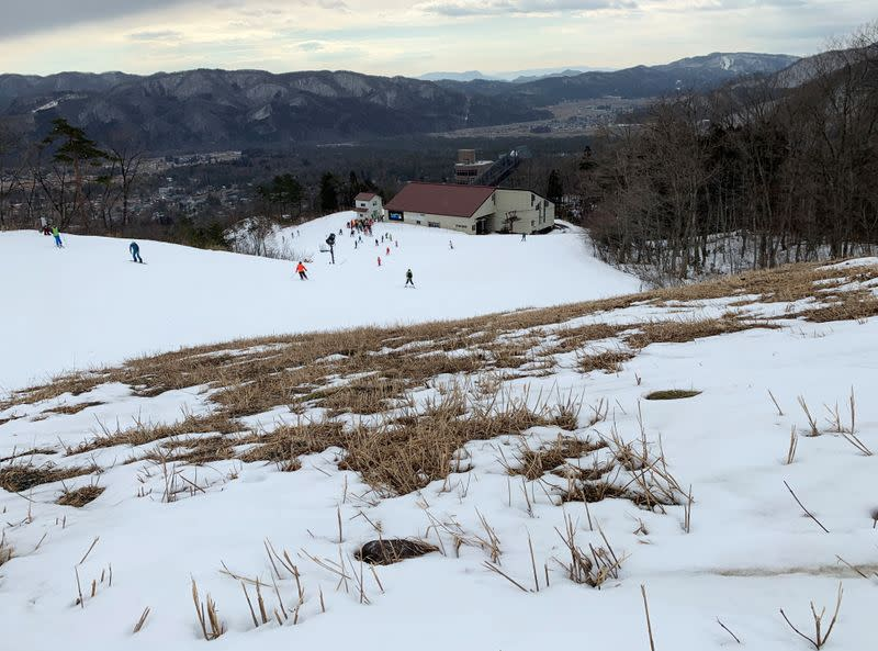 Grass sprouts through the snow as people enjoy skiing at a ski resort in Hakuba village