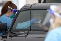 A medical worker swabs a member of the public at a drive-through COVID-19 testing centre in Sydney