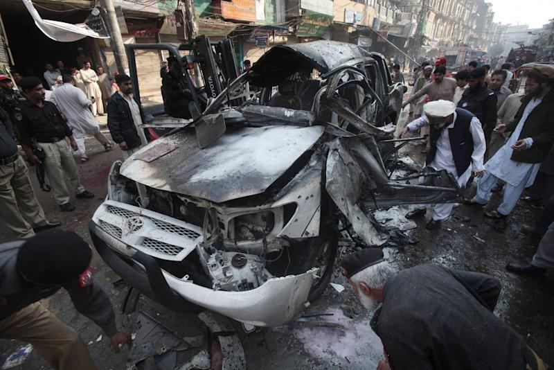 Pakistani police officers and investigators examine a damaged vehicle in Peshawar, Pakistan, Wednesday, Nov. 7, 2012. A  suicide bombing in northwest Pakistan has killed many people and left more than a dozen injured, police said. (AP Photo/Mohammad Sajjad)