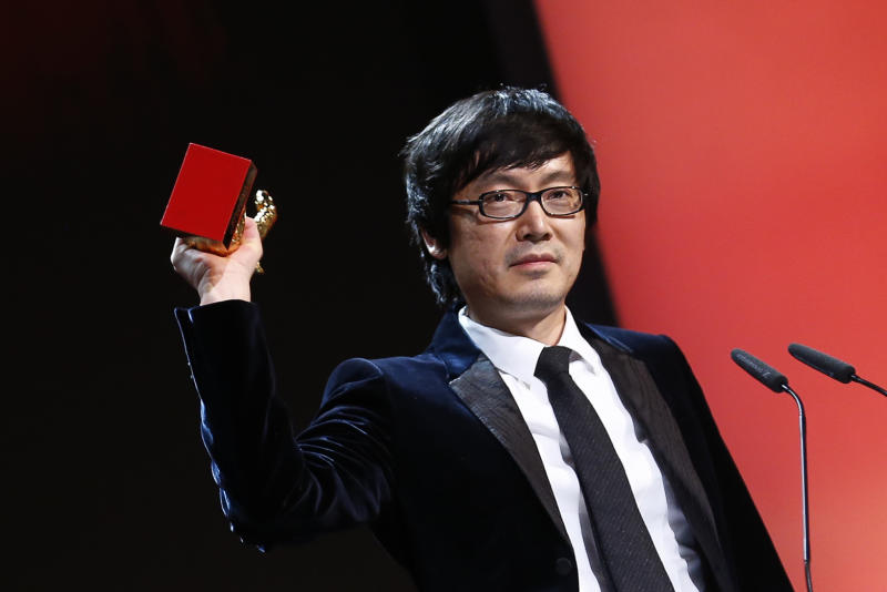 Director Diao Yinan holds aloft the Golden Bear for Best Film for the movie Black Coal, Thin Ice, during the award ceremony at the International Film Festival Berlinale in Berlin, Saturday, Feb. 15, 2014. (AP Photo/Axel Schmidt)