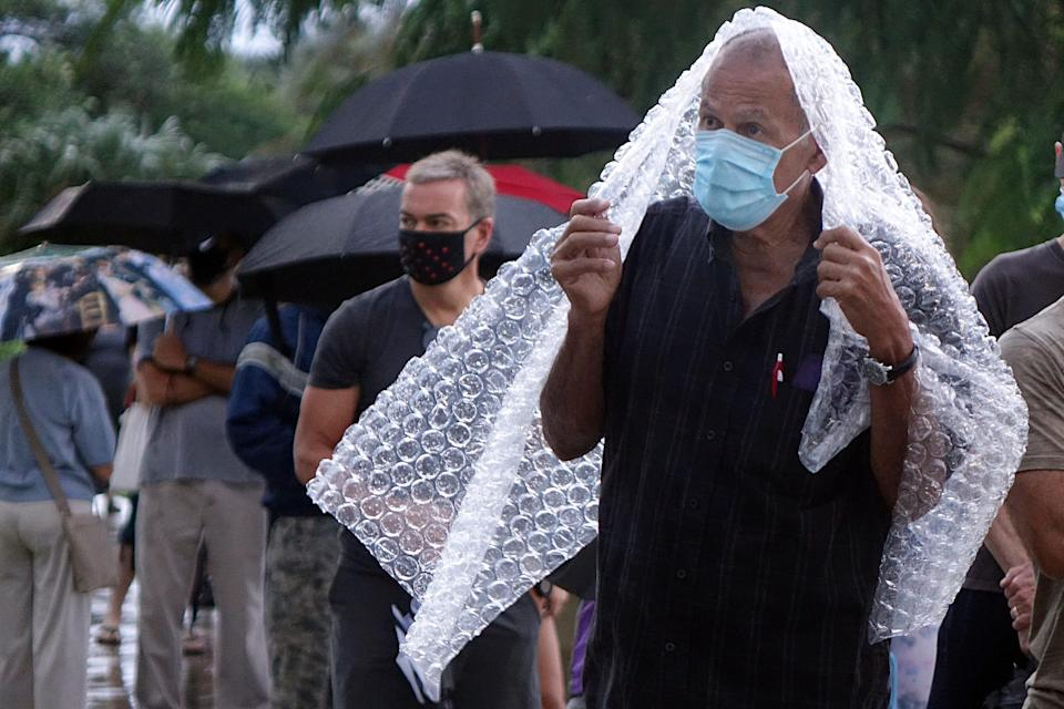 Voters, including Julio Resto, right, of Boca Raton, wait in the rain to vote at the Spanish River Library in Boca Raton, Monday, Oct. 19, 2020, on the first day of early voting in Florida. (Zach Sobiech/South Florida Sun-Sentinel via AP) ORG XMIT: FLLAU602