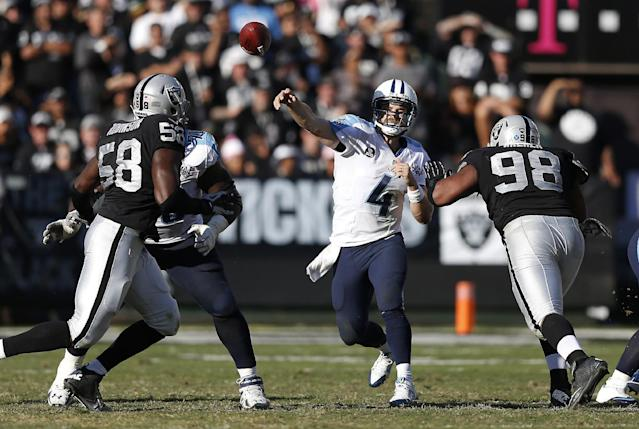 Tennessee Titans quarterback Ryan Fitzpatrick (4) passes between Oakland Raiders defensive end Ryan Robinson (58) and defensive tackle Vance Walker (98) during the second quarter of an NFL football game in Oakland, Calif., Sunday, Nov. 24, 2013. (AP Photo/Beck Diefenbach)