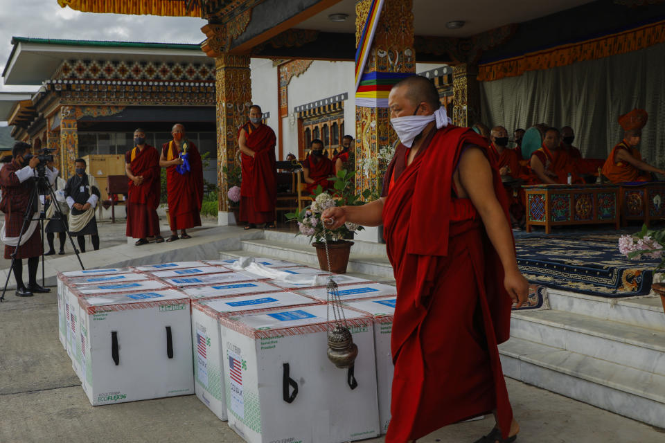 This photograph provided by UNICEF shows monks from Paro's monastic body perform a ritual as 500,000 doses of Moderna COVID-19 vaccine gifted from the United States arrived at Paro International Airport in Bhutan, July 12, 2021. The Himalayan kingdom of Bhutan has fully vaccinated 90% of its eligible adult population within just seven days, its health ministry said Tuesday. (UNICEF via AP)