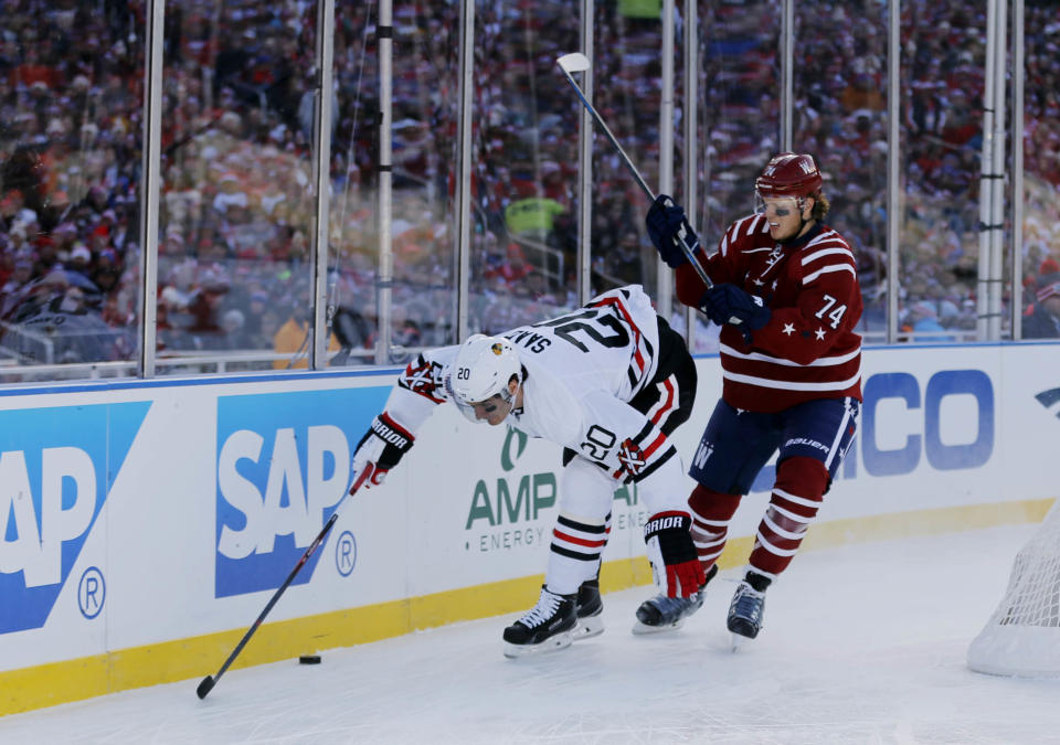 Jan 1, 2015; Washington, DC, USA; Chicago Blackhawks left wing Brandon Saad (20) battles for the puck with Washington Capitals defenseman John Carlson (74) in the first period during the 2015 Winter Classic hockey game at Nationals Park. (Geoff Burke-USA TODAY Sports)