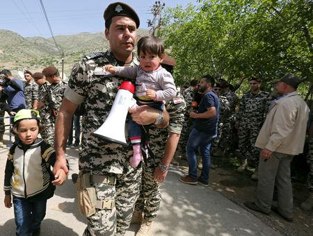 FILE PHOTO: Lebanese general security member holds Syrian refugee children, who fled to Lebanon, as they wait for buses to go back to Syria from the southern village of Shebaa, Lebanon April 18, 2018. REUTERS/Aziz Taher/File Photo