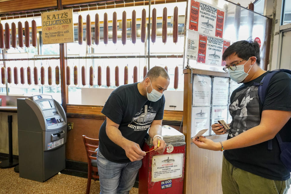 FILE — In this Aug. 17, 2021 file photo, a Katz's Deli employee, left, checks the proof of vaccination from a customer who will be eating inside the restaurant, in New York. New York City's COVID-19 vaccination mandate for restaurants, gyms and entertainment venues is going so well that only 15 businesses have been fined for not enforcing the policy, Mayor Bill de Blasio said Wednesday, Oct. 13, 2021. (AP Photo/Mary Altaffer, File)