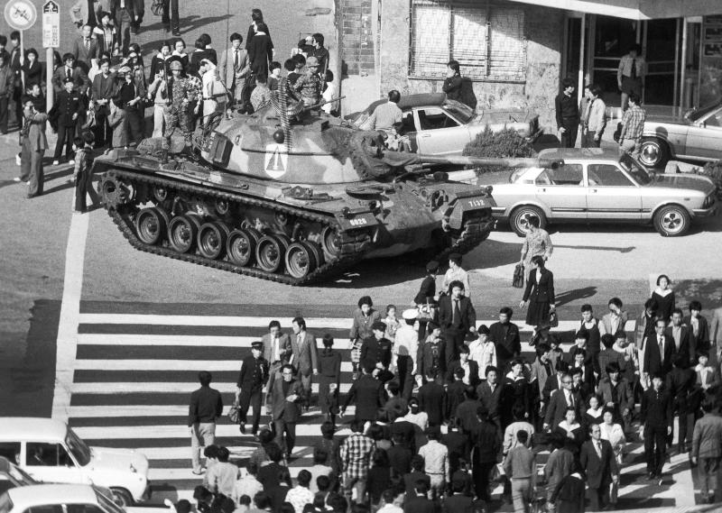 FILE - In this Oct. 27, 1979, file photo, people walk beside a South Korean army tank after the martial law was declared following the death of South Korean President Park Chung-hee in Seoul, South Korea. South Korean President Moon Jae-in's office said Tuesday, July 10, 2018, that Moon has ordered an investigation into an allegation that the military drew up a plan to mobilize troops if protests worsened over the fate of his impeached predecessor last year. (AP Photo/Kim Chon-Kil, File)