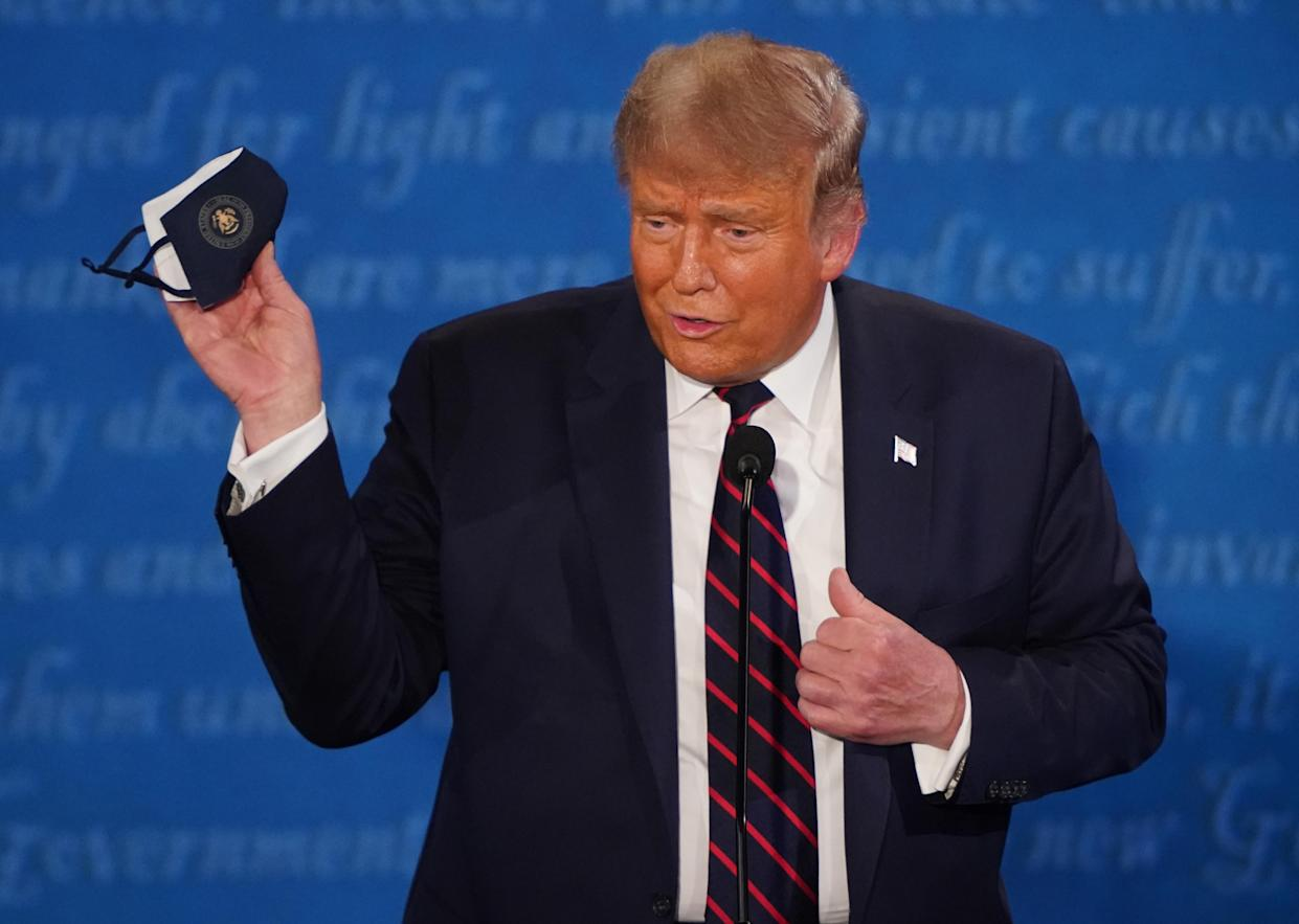 U.S. President Donald Trump holds a protective mask during the first U.S. presidential debate hosted by Case Western Reserve University and the Cleveland Clinic in Cleveland, Ohio, U.S., on Tuesday, Sept. 29, 2020. (Kevin Dietsch/UPI/Bloomberg via Getty Images)
