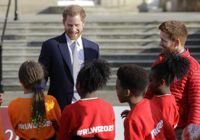 Britain's Prince Harry smiles at schoolchildren in the gardens at Buckingham Palace in London, Thursday, Jan. 16, 2020. Prince Harry, the Duke of Sussex will host the Rugby League World Cup 2021 draw at Buckingham Palace, prior to the draw, The Duke met with representatives from all 21 nations taking part in the tournament, as well as watching children from a local school play rugby league in the Buckingham Palace gardens. (AP Photo/Kirsty Wigglesworth)