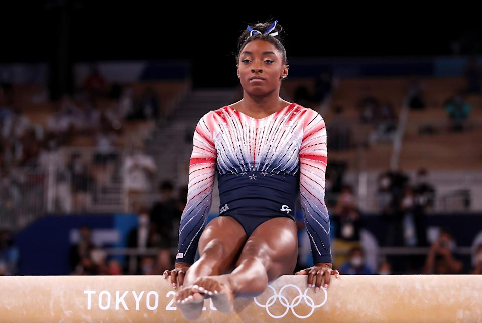 Biles in a seated position on the balance beam with her hands on the beam